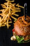 乳酪汉堡用烤肉,乳酪,蕃茄和与黑暗的木表面上的洋葱圈 广告的理想 免版税库存图片
