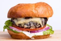 乳酪汉堡用蕃茄,葱,莴苣,在木b的蛋黄酱 库存照片