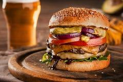 乳酪汉堡,做由与蕃茄切片的黑麦小圆面包和熔化乳酪在烤牛肉和莴苣叶子在木 免版税图库摄影
