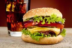 乳酪汉堡,杯播种的照片在木桌上的可乐 库存照片