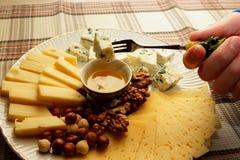 乳酪片断在一把叉子的在人的手上和用完了用他的蜂蜜 图库摄影