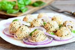 乳酪球用香料和烤芝麻籽服务与未加工的洋葱圈和蓬蒿 库存图片