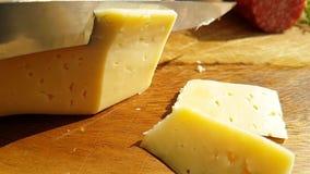 乳酪用在木传统,慢动作射击的一把刀子切开了 股票录像