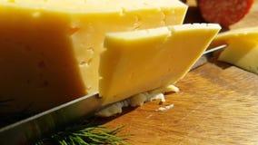 乳酪用在木,慢动作射击的一把刀子切开了 股票视频