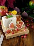 乳酪由羊奶和切片无花果做成在蔓越桔和杏仁围拢的一个木板 库存图片