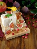 乳酪由羊奶和切片无花果做成在蔓越桔和杏仁围拢的一个木板 图库摄影