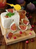 乳酪由羊奶和切片无花果做成在蔓越桔和杏仁围拢的一个木板 免版税库存照片