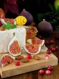 乳酪由羊奶和切片无花果做成在蔓越桔和杏仁围拢的一个木板 免版税图库摄影