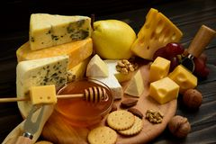 乳酪的各种各样的类型在一张土气木桌上的 免版税库存图片