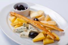 乳酪的各种各样的类型在一块白色板材的 免版税库存照片