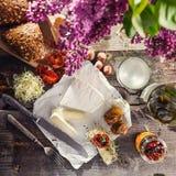 乳酪的咸味干乳酪类型 软制乳酪乳酪 新鲜的咸味干乳酪乳酪和少量切片用小圆面包、干蕃茄、白葡萄酒瓶和玻璃和锂 免版税库存照片