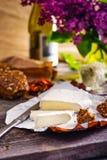乳酪的咸味干乳酪类型 软制乳酪乳酪 新鲜的咸味干乳酪乳酪和少量切片用整粒小圆面包,干蕃茄,白葡萄酒瓶和 免版税库存照片