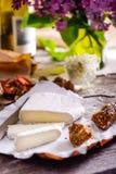 乳酪的咸味干乳酪类型 软制乳酪乳酪 新鲜的咸味干乳酪乳酪和少量切片用整粒小圆面包,干蕃茄,白葡萄酒瓶和 库存图片