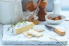 乳酪盘子服务用薄脆饼干、蜂蜜和坚果 在白色木服务板的软制乳酪在白色纹理背景 苹果酱 库存图片