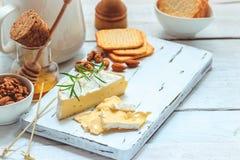 乳酪盘子服务用薄脆饼干、蜂蜜和坚果 在白色木服务板的软制乳酪在白色纹理背景 苹果酱 免版税库存图片