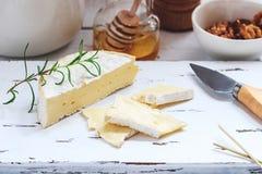 乳酪盘子服务用薄脆饼干、蜂蜜和坚果 在白色木服务板的软制乳酪在白色纹理背景 苹果酱 免版税库存照片
