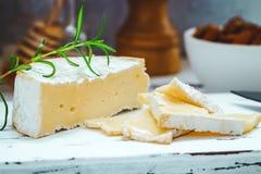 乳酪盘子服务用薄脆饼干、蜂蜜和坚果 在白色木服务板的软制乳酪在白色纹理背景 库存图片