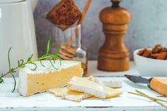 乳酪盘子服务用薄脆饼干、蜂蜜和坚果 在白色木服务板的软制乳酪在白色纹理背景 免版税库存图片