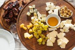乳酪盘子用榛子,蜂蜜,在木桌上的葡萄 免版税库存照片