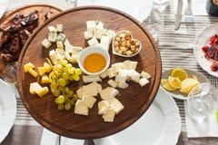乳酪盘子用榛子,蜂蜜,在木桌上的葡萄 库存图片