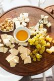 乳酪盘子用榛子,蜂蜜,在木桌上的葡萄 库存照片