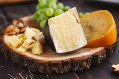 乳酪盛肉盘、巴马干酪在自然木圆盘用葡萄和坚果 库存图片