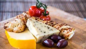 乳酪盛肉盘,开胃小菜,用了卤汁泡橄榄、蕃茄和薄脆饼干在木板,特写镜头 库存图片