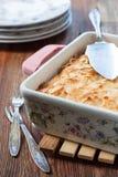 乳酪砂锅在方形的形状的在一张木桌上 免版税图库摄影