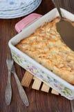 乳酪砂锅在方形的形状的在一张木桌上 免版税库存图片