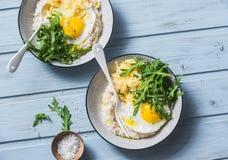 乳酪美味燕麦粥用煎蛋和芝麻菜在蓝色背景,顶视图 健康平衡的早餐 免版税图库摄影