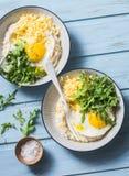 乳酪美味燕麦粥用煎蛋和芝麻菜在蓝色背景,顶视图 健康平衡的早餐 库存图片