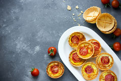 乳酪蕃茄果子馅饼,油酥点心开胃菜,迷你薄饼wi 免版税图库摄影