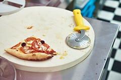 乳酪薄饼片断用蕃茄和一把圆的刀子 免版税库存图片