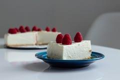 乳酪蛋糕切片用在蓝色板材的莓 与叉子的现有量 在背景的莓乳酪蛋糕 库存照片