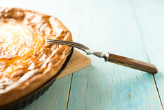乳酪蛋糕和一把叉子在蓝色 免版税库存图片