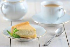 乳酪蛋糕和一片薄荷的叶子在茶碟有一个金黄外缘的 免版税库存图片
