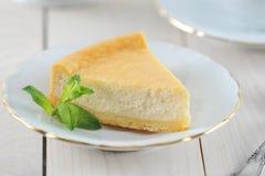 乳酪蛋糕和一片薄荷的叶子在茶碟有一个金黄外缘的 免版税库存照片