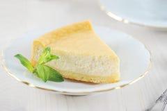 乳酪蛋糕和一片薄荷的叶子在茶碟有一个金黄外缘的 免版税图库摄影