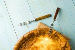 乳酪蛋糕和两把叉子在蓝色 库存照片