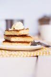 乳酪蛋糕和奶油,黄色餐巾,木板 免版税图库摄影