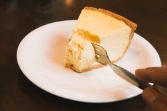 乳酪蛋糕片断在白色板材的在咖啡店 库存图片
