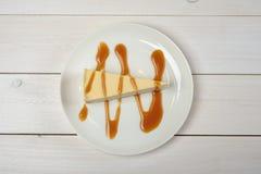 乳酪蛋糕片断,下毛毛雨在站立在木白色桌上的一块白色板材的焦糖调味汁 顶视图 免版税库存图片