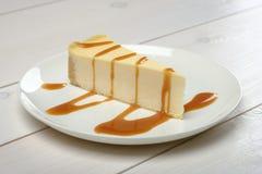 乳酪蛋糕片断,下毛毛雨在站立在木白色桌上的一块白色板材的焦糖调味汁 免版税库存图片