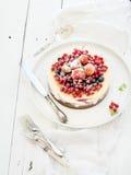 乳酪蛋糕用在上面的新鲜的庭院莓果 库存图片