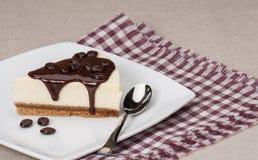 乳酪蛋糕用在白色板材的巧克力汁 免版税库存图片
