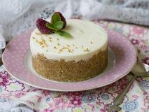 乳酪蛋糕用莓和薄菏在一块桃红色板材在一张木桌上与花卉织品和鞋带 关闭,复制空间 免版税库存图片