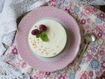 乳酪蛋糕用莓和薄菏在一块桃红色板材在一张木桌上与花卉织品和鞋带 关闭,复制空间 库存图片