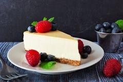 乳酪蛋糕用蓝莓和莓,关闭有黑暗的背景 库存照片