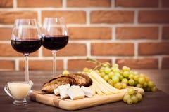 乳酪,敬酒的黑面包,两杯红葡萄酒 免版税库存照片