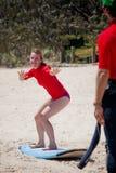 了解白肤金发的女孩冲浪在海滩 免版税库存照片